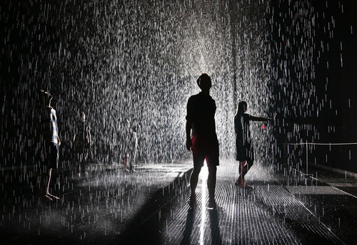 "FILE - In this July 19, 2013 file photo, visitors pace through an environment of falling water at the Random International's ""Rain Room"" at the Museum of Modern Art (MoMA) in New York. In New York, lines were hours-long at the Museum of Modern Art for the chance to experience the Rain Room. Falling rain paused when a human body approached. Watch next year for Oculus Rift, a virtual reality headset that makes players feel like they're inside the game screen.  (AP Photo/Bebeto Matthews, File)"