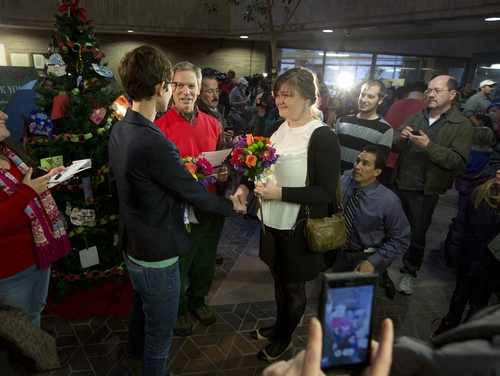 FILE - In this Friday, Dec. 20, 2013, file photo, Natalie Dicou, left, and Nicole Christensen, right, are married by Salt Lake City Mayor Ralph Becker, middle, in the lobby of the Salt Lake County Clerk's Office in Salt Lake City. Utah was expected to ask the U.S. Supreme Court on Tuesday, Dec. 31, 2013, for an emergency stay on more than 900 marriage licenses issued to gay couples since Dec. 20. (AP Photo/Kim Raff, File)