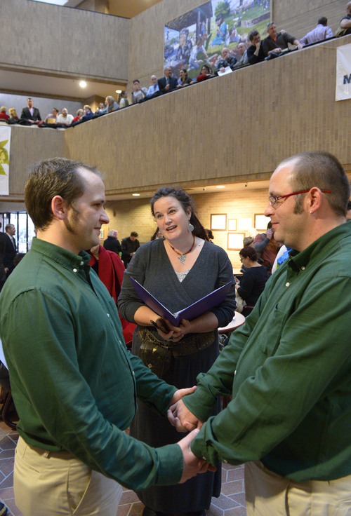 Francisco Kjolseth  |  The Salt Lake Tribune Nathan London, left, marries his partner of 9-years Alan Britton as Allison Ottley performs the ceremony in the lobby of the Salt Lake County Offices on Monday, Dec. 23, 2013. Hundreds of same-sex couples descended on county clerk offices around the state of Utah to request marriage licenses. A federal judge in struck down the state's ban on same-sex marriage last Friday, saying the law violates the U.S. Constitution's guarantees of equal protection and due process.