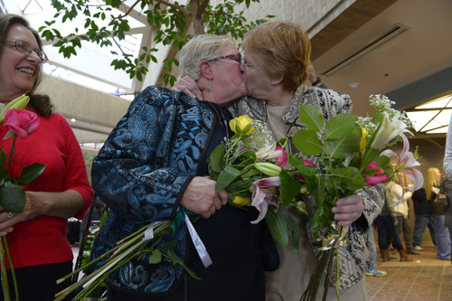 Francisco Kjolseth  |  The Salt Lake Tribune Coral Mangus, 63, center, and her partner of 25-years Andrea Dahl, 56, are married in the lobby of the Salt Lake County offices by Reverend Patty Willis on Monday, Dec. 23, 2013. Mangus and Dahl joined hundreds of other same-sex couples at the Salt Lake County offices to request marriage licenses. Numerous officiants were on hand to perform the wedding ceremonies right after. A federal judge in Utah struck down the state's ban on same-sex marriage last Friday, saying the law violates the U.S. Constitution's guarantees of equal protection and due process.