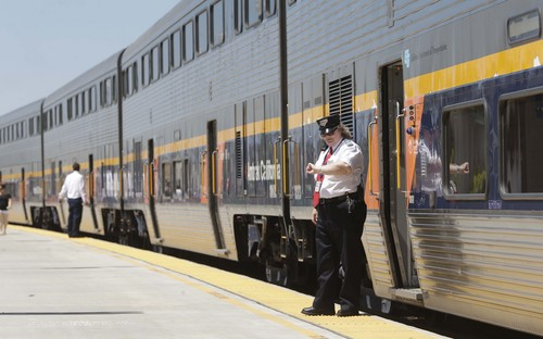 In this photo taken Tuesday, July 16, 2013, an Amtrak conductor checks the time as the passenger train takes on passengers in Hanford, Calif. The state's plan to build the first high-speed rail system in the nation is intended to alleviate gridlock, connect the Central Valley to better jobs, and ease pollution, but many residents oppose the $68 billion project.(AP Photo/Rich Pedroncelli)