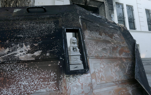 A burned door lies outside the damaged entrance to the Chinese Consulate in San Francisco on Thursday, Jan. 2, 2014. The consulate said in a notice on its website that a person came out of a van parked outside the compound Wednesday night with two buckets of gasoline, poured the fuel on the front of the consulate building and set it on fire. (AP Photo/Jeff Chiu)