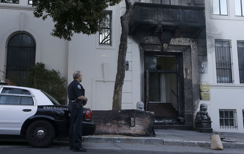 A San Francisco Police officer stands outside of the damaged entrance to the Chinese Consulate in San Francisco on Thursday, Jan. 2, 2014. The consulate said in a notice on its website that a person came out of a van parked outside the compound Wednesday night with two buckets of gasoline, poured the fuel on the front of the consulate building and set it on fire. (AP Photo/Jeff Chiu)