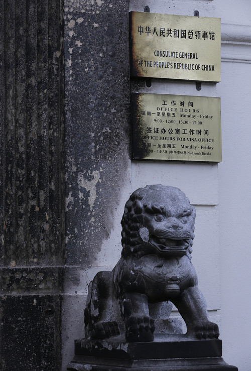 Damage to signs and a lion statue are seen at the entrance of the Chinese Consulate in San Francisco on Thursday, Jan. 2, 2014. The consulate said in a notice on its website that a person came out of a van parked outside the compound Wednesday night with two buckets of gasoline, poured the fuel on the front of the consulate building and set it on fire. (AP Photo/Jeff Chiu)