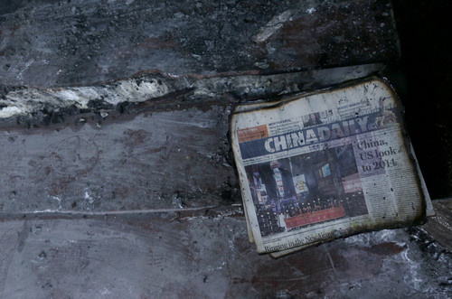 A burned stack of China Daily newspapers sits on a step at the damaged entrance of the Chinese Consulate in San Francisco on Thursday, Jan. 2, 2014. The consulate said in a notice on its website that a person came out of a van parked outside the compound Wednesday night with two buckets of gasoline, poured the fuel on the front of the consulate building and set it on fire. (AP Photo/Jeff Chiu)
