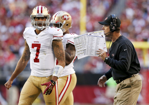 San Francisco 49ers head coach Jim Harbaugh, right, talks with quarterback Colin Kaepernick (7) prior to a play during the first half of an NFL football game against the Arizona Cardinals, Sunday, Dec. 29, 2013, in Glendale, Ariz. (AP Photo/Ross D. Franklin)
