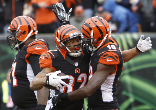 Cincinnati Bengals wide receiver A.J. Green (18) congratulates wide receiver Marvin Jones (82) after Jones caught a 16-yard touchdown pass in the first half of an NFL football game against the Baltimore Ravens, Sunday, Dec. 29, 2013, in Cincinnati. (AP Photo/David Kohl)
