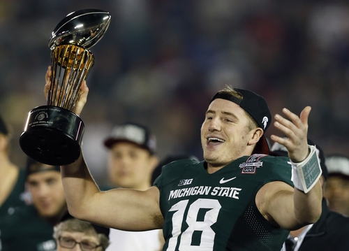 Michigan State quarterback Connor Cook holds the trophy after Michigan State defeated Stanford 24-20 in the Rose Bowl NCAA college football game Wednesday, Jan. 1, 2014, in Pasadena, Calif.  (AP Photo/Danny Moloshok)