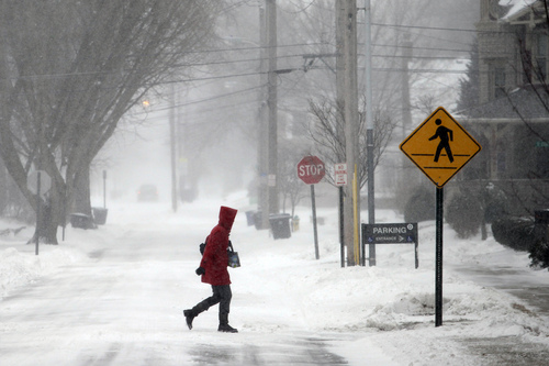 A woman crosses North Summit Street, Thursday, Jan. 2, 2014, on her way to the Wood County Courthouse in Bowling Green, Ohio. A winter weather advisory is in effect for the area. (AP Photo/Sentinel-Tribune, J.D. Pooley) MANDATORY CREDIT, TOLEDO BLADE OUT