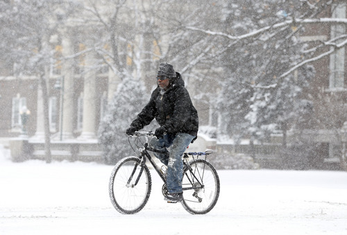A man bikes through the snow on Thursday, Jan. 2, 2014, in Albany, N.Y. Up to 5 inches of snow have fallen in eastern New York early Thursday, but the National Weather Service said some areas from Buffalo to Albany could get up to 12 inches by the time the storm subsides on Friday. (AP Photo/Mike Groll)
