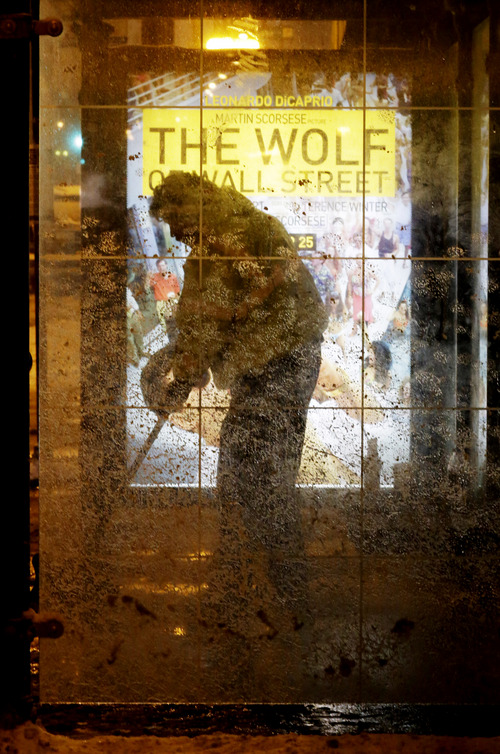 A man clean the snow at a bus stop in downtown Chicago, Wednesday, Jan. 1, 2014. As much as 9 inches of snow has fallen in some parts of the Chicago area since New Year's Eve, and a second wave is expected to dump several more inches by Thursday. (AP Photo/Nam Y. Huh)