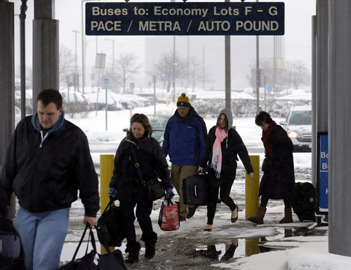 Travelers walk a train station in the economic parking lot at O'Hare International Airport in Chicago, Thursday, Jan. 2, 2014. Another one to three inches of snow could fall across the Chicago metro area Thursday with even more falling in the southern part of the region, according to the National Weather Service. (AP Photo/Nam Y. Huh)