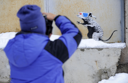Barb Beck of Sandy, Utah, photographs a design by British graffiti artist Banksy on a back door of the Egyptian Theater at the Sundance Film Festival in Park City, Utah, Sunday, Jan. 24, 2010. (AP Photo/Chris Pizzello)