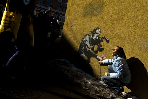 Chris Detrick  |  The Salt Lake Tribune  Festivalgoers take a picture next to a Banksy art work during the Sundance Film Festival in Park City Friday January 21, 2011.