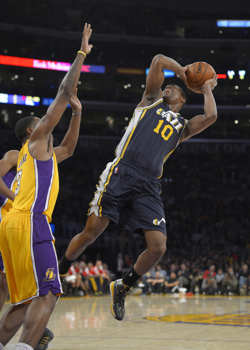Utah Jazz guard Alec Burks, right, puts up a shot as Los Angeles Lakers forward Shawne Williams defends during the first half of an NBA basketball game, Friday, Jan. 3, 2014, in Los Angeles. (AP Photo/Mark J. Terrill)