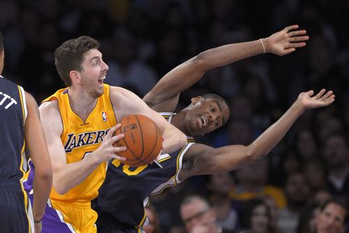 Los Angeles Lakers forward Ryan Kelly, left, looks for a shot as Utah Jazz guard Alec Burks falls during the first half of an NBA basketball game, Friday, Jan. 3, 2014, in Los Angeles. (AP Photo/Mark J. Terrill)