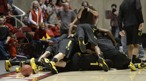 Francisco Kjolseth  |  The Salt Lake Tribune The Oregon Ducks pile on in celebration after beating the Utes in overtime 70 to 68 following game action at the Hunstman Center on the University of Utah campus on Thursday, Jan. 2, 2014.