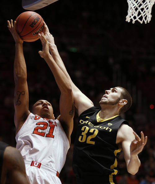 Oregon's Ben Carter, right, blocks the shot of Utah's Jordan Loveridge during the first half of an NCAA college basketball game in Salt Lake City, Thursday, Jan. 2, 2014. (AP photo/George Frey)