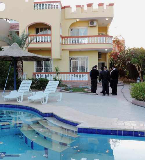 Police stand on a premise of a villa in the Red Sea resort city of Hurghada, Egypt on Friday, Jan. 3, 2014. Authorities said they discovered the bodies of a Swiss couple in the villa, and investigators suspect the villa guard. (AP Photo)