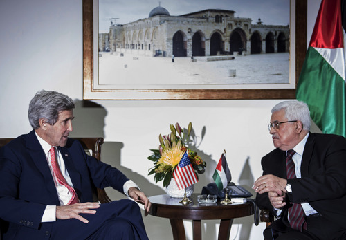 """U.S. Secretary of State John Kerry, left, and Palestinian President Mahmoud Abbas talk before a meeting at the presidential compound in the West Bank city of Ramallah on Friday, Jan. 3, 2014. Kerry took the tenth trip to the region to negotiate a peace deal he claims is """"not mission impossible."""" (AP Photo/Brendan Smialowski, Pool)"""