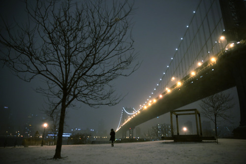 A woman walks through a park on the waterfront in Brooklyn near the Manhattan Bridge during a winter storm in New York, Thursday, Jan. 2, 2014. The storm is expected to bring snow, stiff winds and punishing cold into the Northeast. (AP Photo/Peter Morgan)