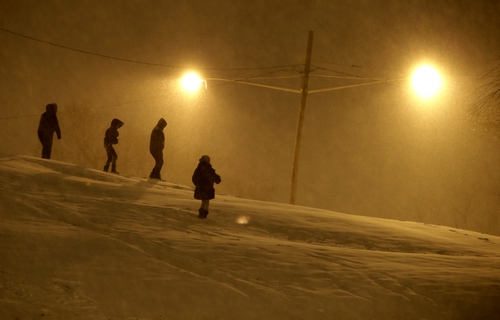 People walk on the snow covered hill of Leonard Gordon Park as snow falls over them, Thursday, Jan. 2, 2014, in Jersey City, N.J. Snow and bone-chilling temperatures are expected for the overnight hours with substantial accumulation predicted. (AP Photo/Julio Cortez)