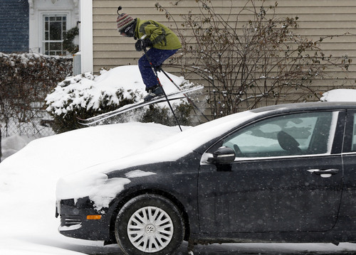 Milo Bloom, 10, skis over a snowbank next to a parked car during a snowstorm, Thursday, Jan. 2, 2014, in Portland, Maine. Strong winds are creating blizzard-like conditions. A wind chill factor of 30 degrees below zero is expected Friday. (AP Photo/Robert F. Bukaty)