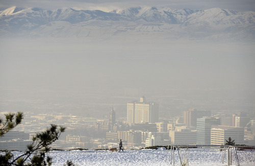 Al Hartmann  |  The Salt Lake Tribune Woman walks her dog along the track at 11th Avenue Park just above the polluted air buiding up in dowtntown Salt Lake City Monday morning December 30.  The Utah Division of Air Quality rated the air in the orange range with a health advisory for elderly and persons with existing heart or lung disease to stay indoors and reduce physical activity.
