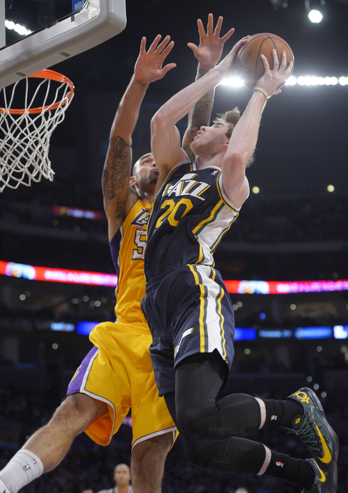 Utah Jazz guard Gordon Hayward, right, goes up for a shot as Los Angeles Lakers center Robert Sacre defends during the first half of an NBA basketball game, Friday, Jan. 3, 2014, in Los Angeles. (AP Photo/Mark J. Terrill)