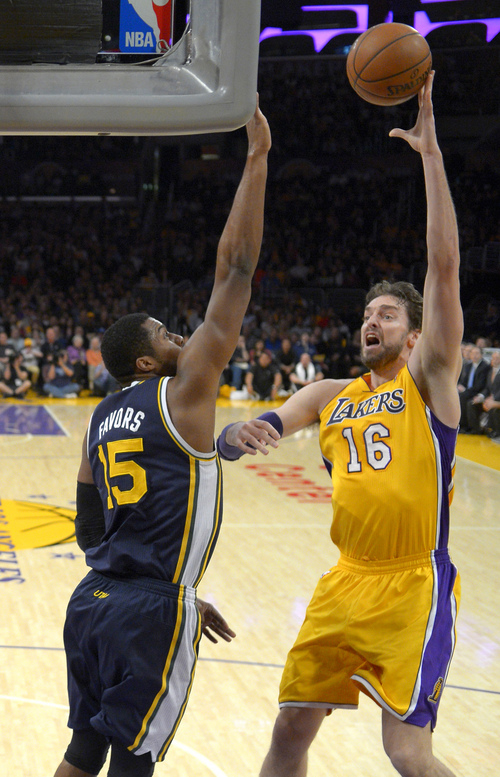 Los Angeles Lakers center Pau Gasol, right, of Spain, puts up a shot as Utah Jazz forward Derrick Favors defends during the first half of an NBA basketball game, Friday, Jan. 3, 2014, in Los Angeles. (AP Photo/Mark J. Terrill)