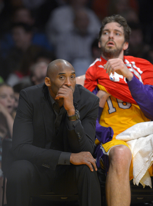Los Angeles Lakers guard Kobe Bryant, left, watches from the bench along with center Pau Gasol, of Spain, during the first half of an NBA basketball game against the Utah Jazz, Friday, Jan. 3, 2014, in Los Angeles. (AP Photo/Mark J. Terrill)