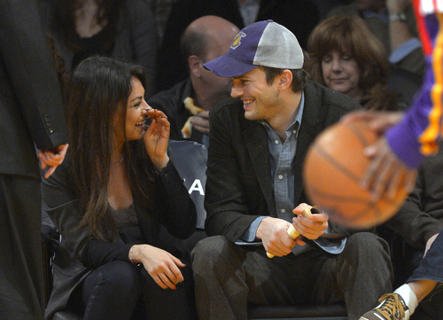 Actors Mila Kunis and Ashton Kutcher talk prior to the Los Angeles Lakers' NBA basketball game against the Utah Jazz, Friday, Jan. 3, 2014, in Los Angeles. (AP Photo/Mark J. Terrill)