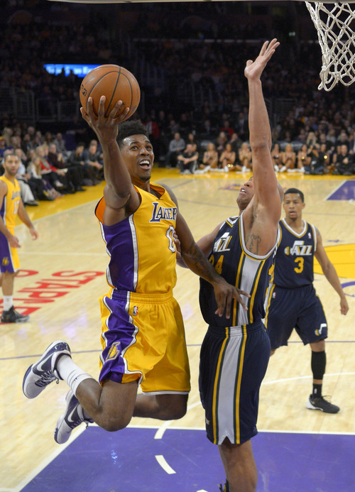 Los Angeles Lakers forward Nick Young, left, puts up a shot as Utah Jazz forward Richard Jefferson defends during the first half of an NBA basketball game, Friday, Jan. 3, 2014, in Los Angeles. (AP Photo/Mark J. Terrill)