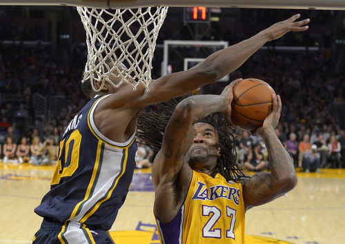 Los Angeles Lakers center Jordan Hill, right, looks to shoot as Utah Jazz forward Jeremy Evans defends during the first half of an NBA basketball game, Friday, Jan. 3, 2014, in Los Angeles. (AP Photo/Mark J. Terrill)