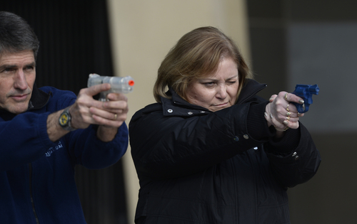 Rick Egan  | The Salt Lake Tribune   Cavett Eaton (left) and Deanna Taylor (right) practice with plastic gun replicas during a role-playing exercise, as part of a free concealed firearms permit class to Utah educators at the Salt Lake City Library, Friday, January 3, 2014.