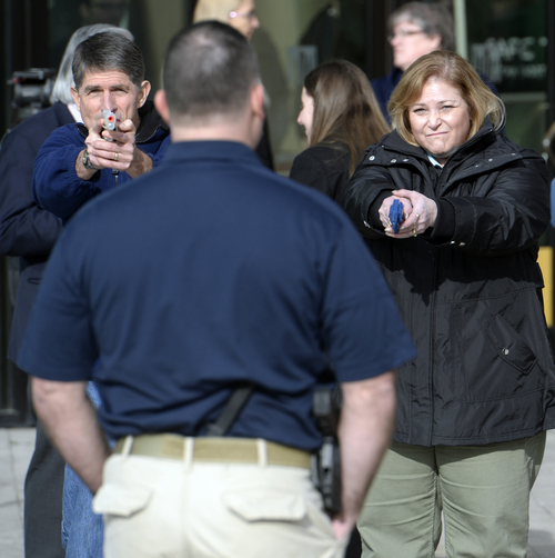 Rick Egan  | The Salt Lake Tribune   Cavett Eaton (left) and Deanna Taylor (right) point a plastic gun replica at Clark Aposhian, during a role-playing exercise, as part of a free concealed firearms permit class to Utah educators at the Salt Lake City Library, Friday, January 3, 2014.