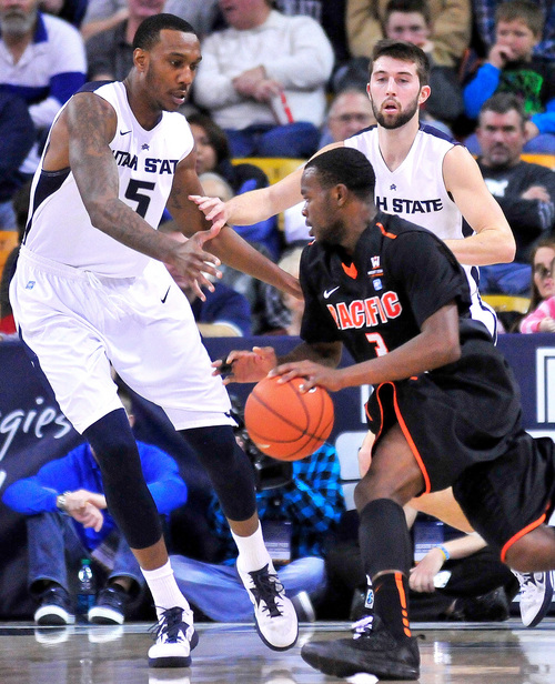 Pacific's Sama Taku, front right, drives around Utah State's Jarred Shaw (5) and Preston Medlin during an NCAA college basketball game on Saturday, Dec. 7, 2013, in Logan, Utah. (AP Photo/Herald Journal, John Zsiray)