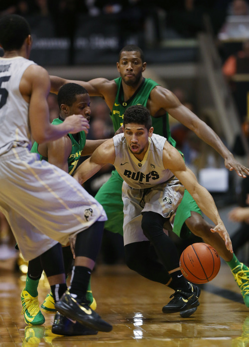 Colorado guard Askia Booker, front, right, is trapped with the ball by Oregon guard Johnathan Loyd, front left, and forward Mike Moser in the second half of Colorado's 100-91 victory in an NCAA college basketball game on Sunday, Jan. 5, 2014, in Boulder, Colo. (AP Photo/David Zalubowski)