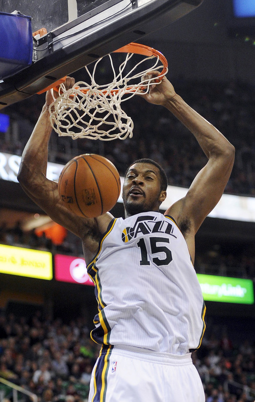 Utah Jazz's Derrick Favors (15) slams home two points in the final minute of an NBA basketball game against the Charlotte Bobcats, Monday, Dec. 30, 2013, in Salt Lake City. (AP Photo/Gene Sweeney Jr.)