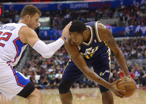 Los Angeles Clippers power forward Blake Griffin, left, puts his hand on the head of Utah Jazz power forward Derrick Favors during the first half of their preseason NBA basketball game on Wednesday, Oct. 23, 2013, in Los Angeles. (AP Photo/Mark J. Terrill)