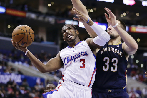 Los Angeles Clippers' Chris Paul, left, goes up for a basket against New Orleans Pelicans' Ryan Anderson during the second half of an NBA basketball game on Wednesday, Dec. 18, 2013, in Los Angeles. The Clippers won 108-95. (AP Photo/Jae C. Hong)