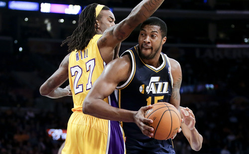 Utah Jazz forward Derrick Favors, right, drives to the basket around Los Angeles Lakers center Jordan Hill during the first half of a preseason NBA basketball game in Los Angeles, Tuesday, Oct. 22, 2013. (AP Photo/Chris Carlson)