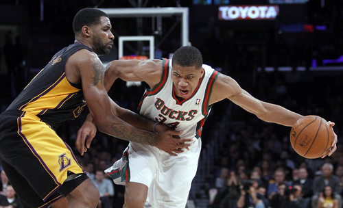 Milwaukee Bucks shooting guard Giannis Antetokounmpo, right, drives against Los Angeles Lakers forward Shawne Williams during the second half of an NBA basketball game Tuesday, Dec. 31, 2013, in Los Angeles. The Bucks won 94-79. (AP Photo/Alex Gallardo)