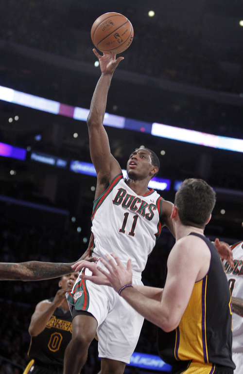 Milwaukee Bucks guard Brandon Knight (11) releases a floater against Los Angeles Lakers forward Nick Young, left, and forward Ryan Kelly, right, during the second half of an NBA basketball game Tuesday, Dec. 31, 2013, in Los Angeles. The Bucks won 94-79. (AP Photo/Alex Gallardo)
