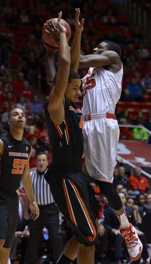 Leah Hogsten  |  The Salt Lake Tribune Utah Utes guard Delon Wright (55) hits the net over Oregon State Beavers guard Challe Barton (4).The University of Utah defeated Oregon State 80-69 during their game Saturday, January 4, 2014 at the Huntsman Center.
