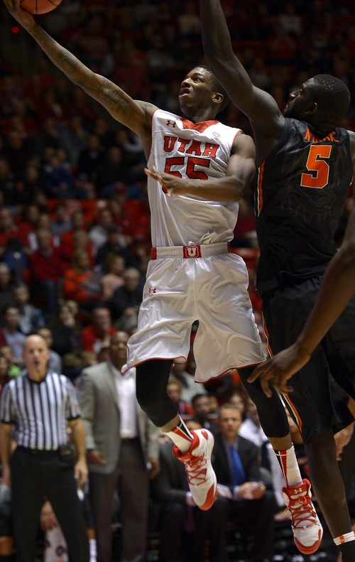 Leah Hogsten  |  The Salt Lake Tribune Utah Utes guard Delon Wright (55) rounds Oregon State Beavers center Cheikh N'diaye (5) for two. The University of Utah defeated Oregon State 80-69 during their game Saturday, January 4, 2014 at the Huntsman Center.