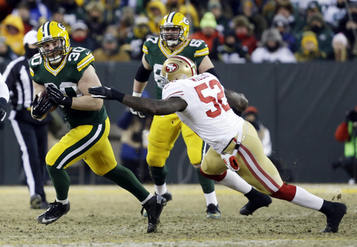 Green Bay Packers fullback John Kuhn (30) runs against San Francisco 49ers inside linebacker Patrick Willis (52) after receiving a pass from quarterback Aaron Rodgers during the first half of an NFL wild-card playoff football game, Sunday, Jan. 5, 2014, in Green Bay, Wis. (AP Photo/Mike Roemer)