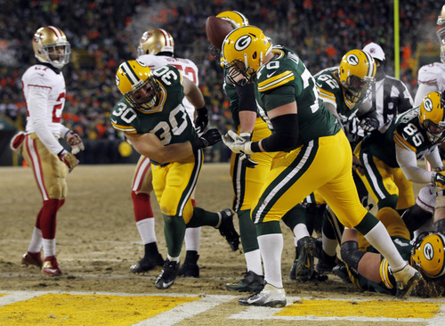 Green Bay Packers fullback John Kuhn (30) spikes the ball after making a touchdown run during the second half of an NFL wild-card playoff football game against the San Francisco 49ers, Sunday, Jan. 5, 2014, in Green Bay, Wis. (AP Photo/Mike Roemer)