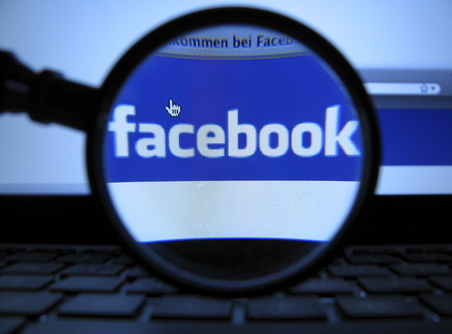 FILE - In this Oct. 10, 2011 file photo, a magnifying glass is posed over a monitor displaying a Facebook page in Munich. (AP Photo/dapd, Joerg Koch)