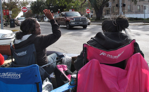 Keisha Moore, an aunt of 17-year-old Kendrick Johnson, waves at passing traffic as she sits with the teenager's mother, Jacquelyn Johnson, outside the Lowndes County courthouse in Valdosta, Ga., on Dec. 13, 2013. Kendrick Johnson was found dead inside a rolled-up wrestling mat on Jan. 11, 2013, and his family has rejected investigators' conclusion that he died in an accident. The teenagers' parents and relatives have been camping out with protest signs outside the courthouse every weekday for months.  (AP Photo/Russ Bynum)
